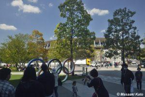 ビル陰に設置された五輪モニュメントと国立競技場 2021年4月11日撮影、新宿区霞岳町